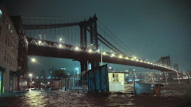 FILE - In this Oct. 29, 2012 file photo, streets in the Brooklyn borough of New York are flooded under the Manhattan Bridge as a surge of seawater is pushed into New York City by Superstorm Sandy. The weather in 2012 was deadly, costly and record-breaking everywhere _ but especially in the United States. (AP Photo/Bebeto Matthews, File)