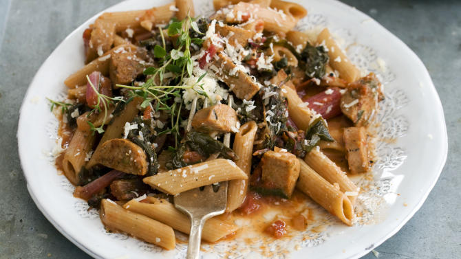 In this image taken on April 15, 2013, whole-wheat penne with spring greens and sausage is shown served on a plate in Concord, N.H. (AP Photo/Matthew Mead)