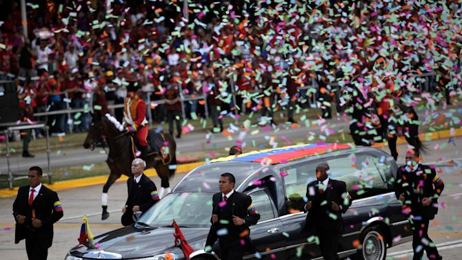 Body guards runs next to the hearse carrying the coffin that contains the remains of Venezuela's late President Hugo Chavez, in a second funeral procession, in Caracas, Venezuela, Friday, March 15, 2013. Chavez's body is being transferred Friday from the military academy where it has been lying in state to the military museum that will serve as his final resting place. Venezuelans lined up to bid their last farewell to Hugo Chavez on Friday. Chavez was 58 when he died of an undisclosed type of cancer on March 5. (AP Photo/Rodrigo Abd)