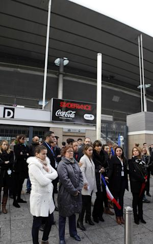 People stand for a minute of silence outside the Stade …