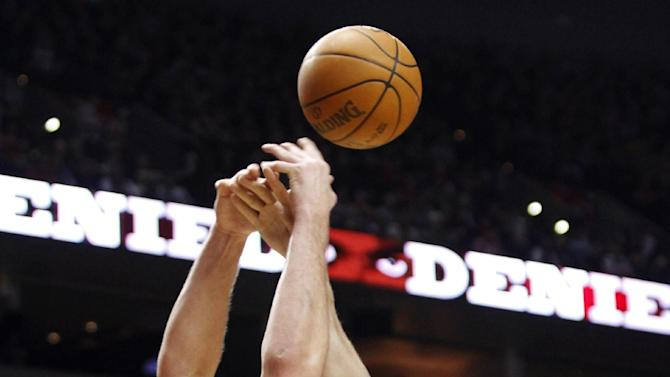 Minnesota Timberwolves center Nikola Pekovic, right, fights for a rebound with Portland Trail Blazers center Joel Przybilla during the first quarter of their NBA basketball game in Portland, Ore., Saturday, March 3, 2012. (AP Photo/Don Ryan)