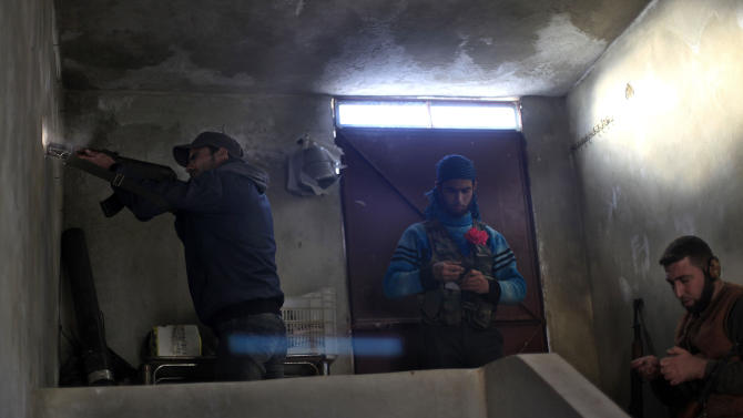 FILE - In this Saturday, Nov. 17, 2012 file photo, a Syrian fighter fires his weapon during clashes with Syrian army forces in town of Harem on the outskirts of Idlib, Syria. Through mid-2012, rebel power grew and Assad's army ramped up its response. Relentless government shelling leveled neighborhoods and killed hundreds. Regular reports emerged of mass killings by the regime or thugs loyal to it, pushing more Syrians toward armed struggle. The government, which considers the opposition terrorist gangs backed by foreign powers, denied any role, and does not respond to requests for comment on its military. The rebels, too, were accused of atrocities. (AP Photo/ Khalil Hamra, File)