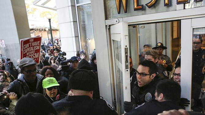 Police scuffle with Black Lives Matter protesters while attempting to close a door to Westlake Mall on Black Friday in Seattle, Washington