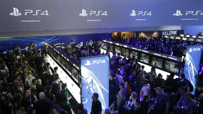 FILE - In this June 11, 2013 file photo, show attendees play video games on the new Sony PlayStation 4 at the Sony booth during the Electronic Entertainment Expo, in Los Angeles. With the launch of the Xbox One, PlayStation 4 and Wii U in the video game industry's rearview mirror, the spotlight at the Electronic Entertainment Expo, held June 10-12, 2014, is expected to shift back to games. From online-only titles to virtual reality experiences, about 200 exhibitors will hype their latest software in hopes of driving away from E3 with The Next Big Thing. (AP Photo/Jae C. Hong, file)