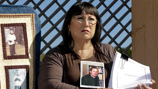 Survivor Esther Miller, holds newly released files of her perpetrator Rev. Deacon Michael Nocita, seen in middle picture, as she joins  Members of SNAP, the Survivors Network of those Abused by Priests during a news conference outside the Cathedral of Our Lady of the Angels in Los Angeles, Friday, Feb. 1, 2013. Cardinal Roger Mahony of the largest Roman Catholic archdiocese in the United States was stripped of his duties in an unprecedented move by his successor Archbishop Jose Gomez, who described the church's actions during the growing sex abuse scandal as evil. (AP Photo/Damian Dovarganes)