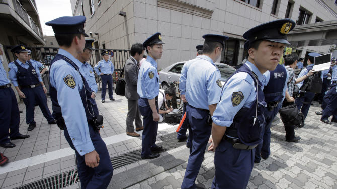 Police officers stand guard at Kamata Police in Tokyo where Katsuya Takahashi, the last fugitive suspected in a doomsday cult's deadly nerve gas attack on Tokyo subways 17 years ago, was taken in Friday, July 15, 2012, after he was arrested at a nearby comic book cafe earlier in the day. Takahashi, 54, a former member of Aum Shinrikyo cult, was arrested on suspicion of murder in the 1995 attack, which killed 13 people and injured more than 6,000. (AP Photo/Itsuo Inouye)