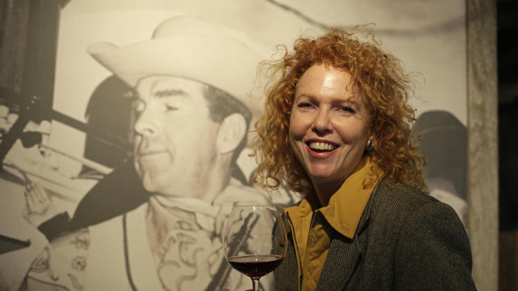 "In this photo taken March 15, 2013 Kate MacMurray, daughter of the late actor Fred MacMurray poses with a glass of Pinot Noir by a photograph of her father in a tasting area and gallery of old photographs at the MacMurray Ranch in Healdsburg, Calif. The former cattle ranch, which was purchased in 1941 by the actor in the popular TV series ""My Three Sons,"" now produces wine and is owned by the Gallo wine family. (AP Photo/Eric Risberg)"