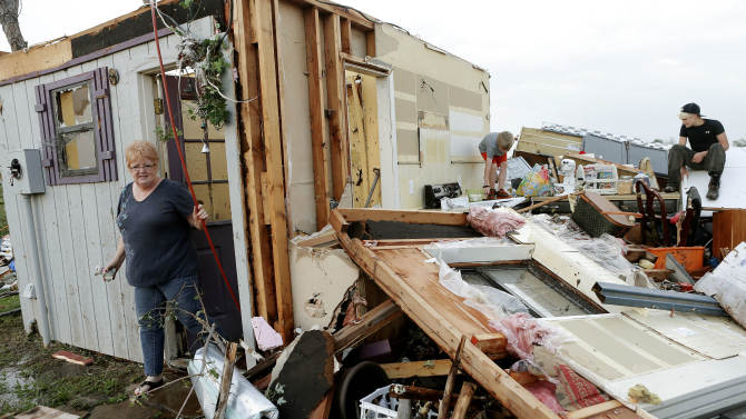 Marlena Hodson walks out of her home as her grandsons, Campbell Miller, 10, and Dillon Miller, 13, at right, help her sort through belongings after a tornado damaged her home in Carney, Okla., Sunday, May 19, 2013. Hodson and her family left the home to escape the tornado. (AP Photo/The Oklahoman, Bryan Terry)