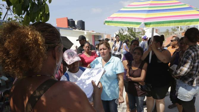A resident speaks to people that were evacuated, inside a school used as a shelter in Cabo San Lucas, after Hurricane Odile hit in Baja California