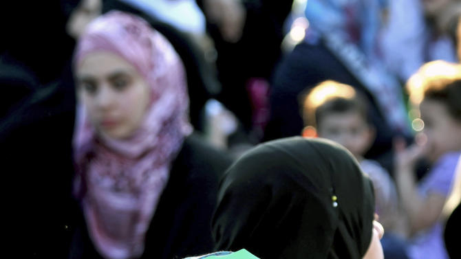 Syrian women wait for the Eid al-Fitr prayer in front of the Syrian embassy in Amman, Jordan, Sunday, Aug. 19, 2012. Muslims around the world celebrate Eid al-Fitr, marking the end of Ramadan, the Muslim calendar's ninth and holiest month during which followers are required to abstain from food and drink from dawn to dusk. (AP Photo/Mohammad Hannon)