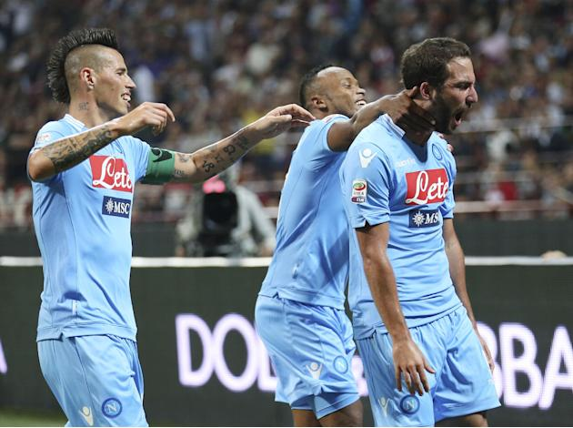 Napoli forward Gonzalo Higuain, right, of Argentina, celebrates with his teammates Marek Hamsik, left, and Camilo Zuniga, of Colombia, after scoring during the Serie A soccer match between AC Milan an