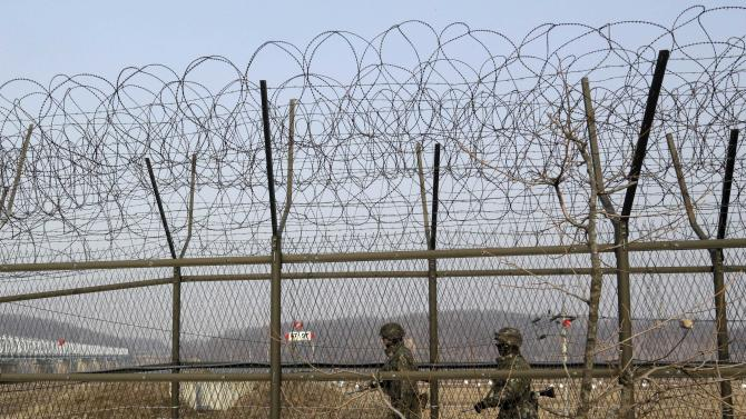 South Korean army soldiers patrol along a barbed-wire fence at the Imjingak Pavilion near the border village of Panmunjom, which has separated the two Koreas since the Korean War, in Paju, north of Seoul, South Korea, Wednesday, March 6, 2013. North Korea's military is vowing to cancel the 1953 cease-fire that ended the Korean War, straining already frayed ties between Washington and Pyongyang as the United Nations moves to impose punishing sanctions over the North's recent nuclear test. (AP Photo/Lee Jin-man)