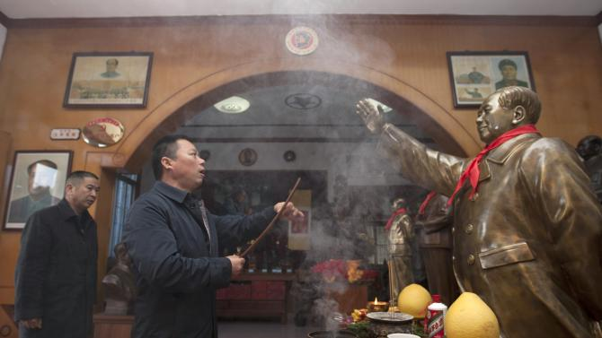 Tian Haiming, a sculptor, burns incense in front of a copper statue of China's late Chairman Mao Zedong before handing it to the buyer,  in Shaoshan