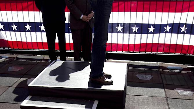 Republican presidential candidate, former Massachusetts Gov. Mitt Romney casts a shadow as he speaks on the roof of an office building in Harrisburg, Pa., Thursday, April 5, 2012. (AP Photo/Steven Senne)