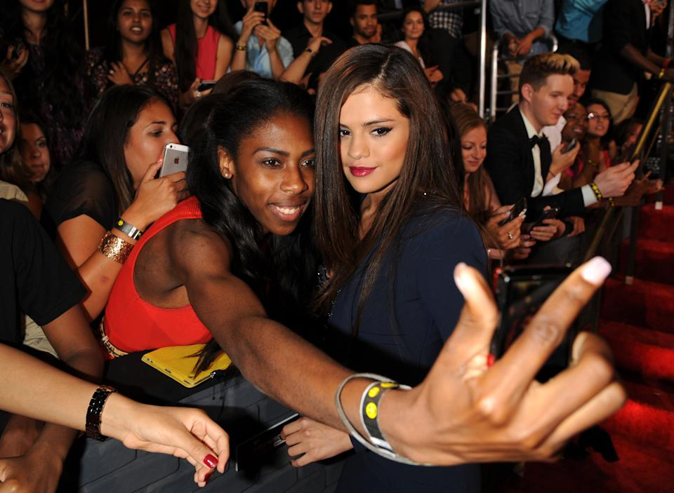 Selena Gomez poses with a fan at the MTV Video Music Awards on Sunday, Aug. 25, 2013, at the Barclays Center in the Brooklyn borough of New York. (Photo by Scott Gries/Invision/AP)