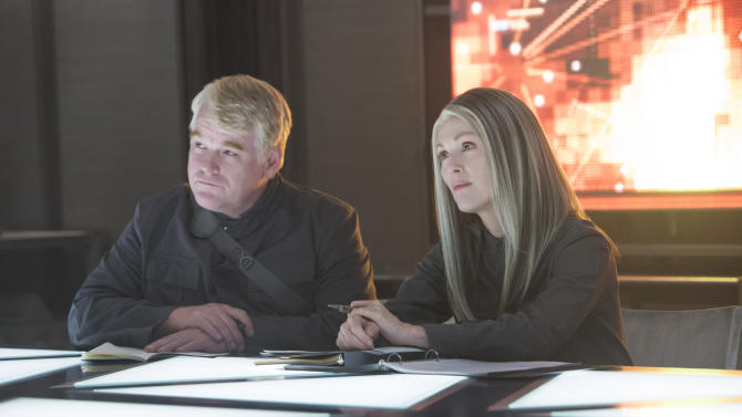 """This photo released by Lionsgate shows, Philip Seymour Hoffman, left, as Plutarch Heavensbee and Julianne Moore as President Coin in a scene from the film, """"The Hunger Games: Mockingjay - Part 1."""" The movie releases on Nov. 21, 2014. (AP Photo/Lionsgate, Murray Close)"""
