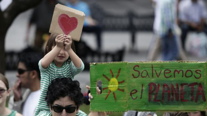 A girl holds a picture of a heart during a march to demand politicians take tougher action to protect against climate change in Guadalajara