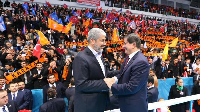 Senior Hamas leader Mashal shakes hands with Turkish Prime Minister Davutoglu during a meeting of Turkey's ruling AK Party in the central Anatolian city of Konya