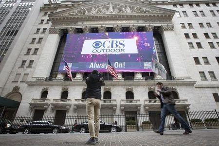 A man takes a photo of a CBS Outdoor banner displayed on the facade of the New York Stock Exchange