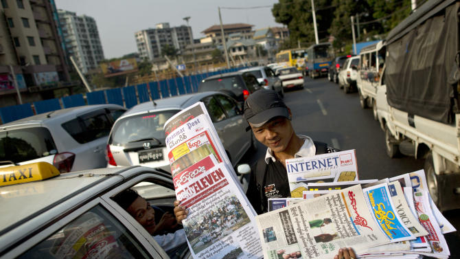 A vendor sells newspapers to motorists during a traffic jam in Yangon, Myanmar, Monday, April 1, 2013. For most people in Myanmar, it will be a novelty when privately run daily newspapers hit the streets on Monday. Many weren't even born when the late dictator Ne Win imposed a state monopoly on the daily press in the 1960s.(AP Photo/Gemunu Amarasinghe)