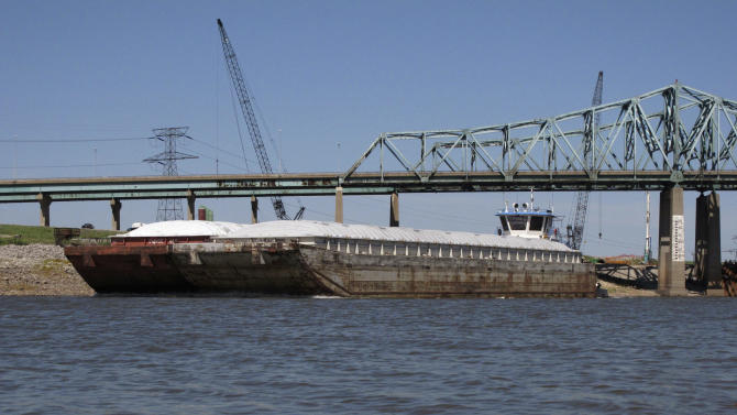 FILE - In this Sept. 19, 2012 file photo, a barge eases southbound in a Mississippi River channel toward a lock that remained shut down in Granite City, Ill., causing a traffic jam of dozens of tugboats and hundreds of barges. That same site was the scene of a 17-hour shutdown Tuesday, Jan. 22, 2013, after a barge got caught up in and damaged an auxiliary lock. A key stretch of the Mississippi River reopened to shipping Wednesday after hasty repairs were made to a lock damaged by a barge, marking the latest victory for stewards of the drought-plagued waterway they have maneuvered to keep open. (AP Photo/Jim Suhr, File)