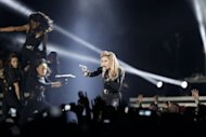 US singer Madonna performs on stage at the Stade de France in the Paris suburb of Saint-Denis on July 14 during her MDNA world tour. Madonna is courting controversy again ahead of an August 1 gig in Warsaw, having already been threatened with legal action in France for projecting a swastika on an image of far-right party leader Marine Le Pen