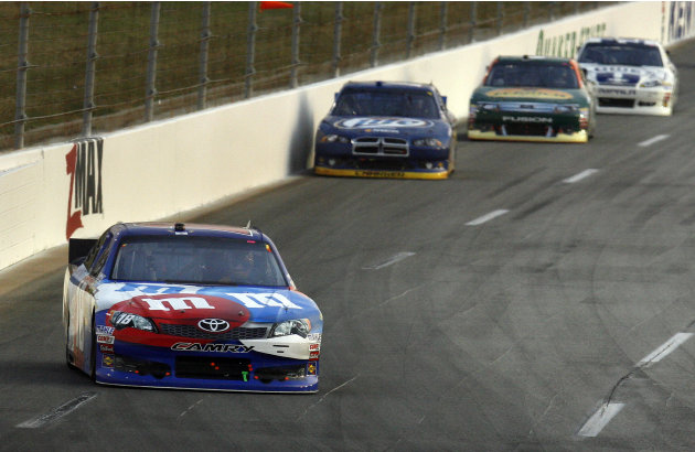 Kyle Busch leads Brad Keselowski, Aric Almirola and Jimmie Johnson, from left, into the third turn during the NASCAR Sprint Cup Series auto race at Kentucky Speedway in Sparta, Ky., Saturday, June 30,
