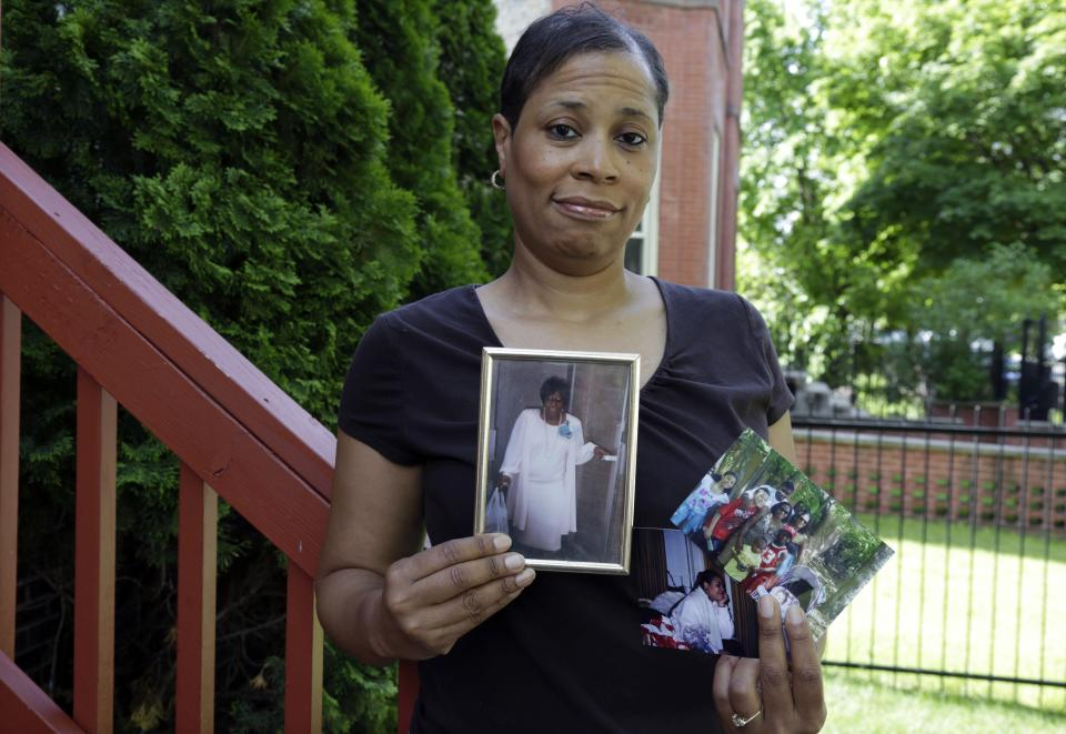 In this May 31, 2013 photo, breast cancer survivor Alicia Cook holds photos of family members who have also been afflicted by breast cancer, outside her home in Chicago. New research shows genetic breast cancer is more common in black women than previously thought. (AP Photo/M. Spencer Green)