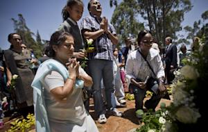 Relatives of those who died lay white roses and pray …