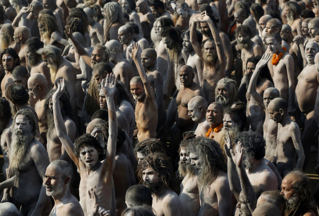Indian Hindu holy men, some covered in ash, walk in procession after bathing at Sangam, the confluence of the Ganges, Yamuna and mythical Saraswati River, during the Maha Kumbh festival, in Allahabad,