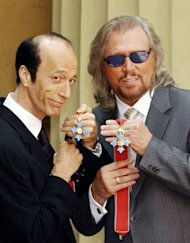 Bee Gees members Robin (L) and Barry Gibb hold their CBE's after receiving them from the Prince of Wales at Buckingham Palace, London in 2004
