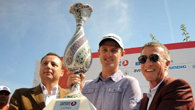 Justin Rose (C) of England poses with the trophy after winning the Turkish Airlines World Golf Final final Day at Antalya GC
