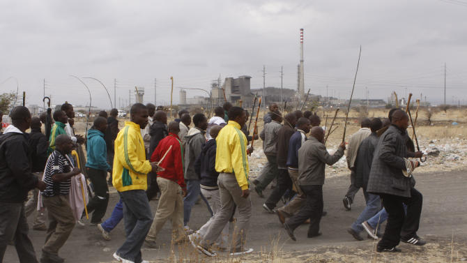 Striking mine workers march to the Karee  shaft at the Lonmin Platinum Mine near Rustenburg, South Africa Wednesday, Sept. 5, 2012 to hand over a memorandum to mine management. Miners are refusing to return to work  until their demands  over low pay and working conditions are met. Three weeks ago 34 miners were shot and killed by police. (AP Photo/Denis Farrell)