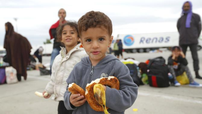 A young child eats a banana as migrants wait for buses after crossing Austrian border in Nickelsdorf