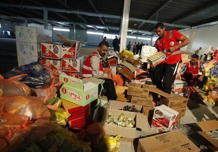 Libyan Red Crescent workers prepare parcels of food aid to be delivered to civilians fleeing violence in the eastern city of Benghazi, in Misrata
