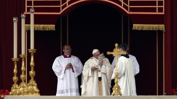 Pope Francis kisses the relic of Pope John Paul II during a solemn ceremony in St. Peter's Square at the Vatican, Sunday, April 27, 2014. Pope Francis has declared his two predecessors John XXIII and John Paul II saints in an unprecedented canonization ceremony made even more historic by the presence of retired Pope Benedict XVI. (AP Photo/Domenico Stinellis)