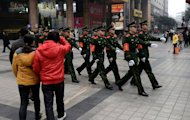 Chinese paramilitary police march through the shopping area of Chongqing, February 3, 2013. A year after Chongqing&#39;s police chief set off China&#39;s biggest scandal in decades, the megacity has seen revelations of torture, corruption and rights abuses, but little revolutionary change