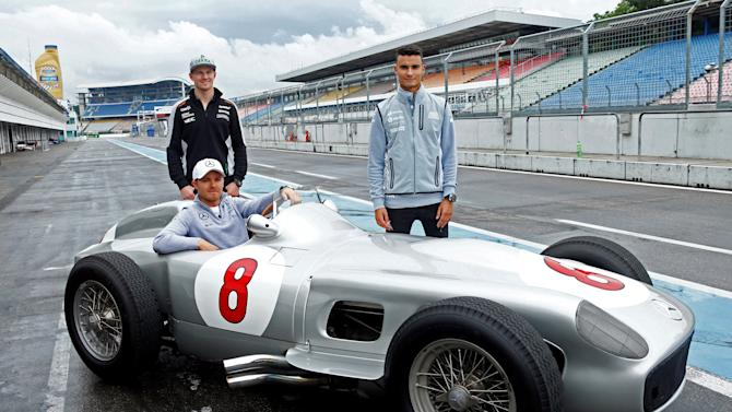 Formula One drivers Hulkenberg, Rosberg, and Wehrlein pose next to a Mercedes W196 R during the Mercedes Benz media day at the Hockenheim racing circuit