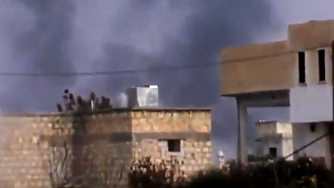In this image taken from video obtained from the Shaam News Network, which has been authenticated based on its contents and other AP reporting, smoke rises from buildings in Taftanaz village, Idlib province, northern Syria, on Wednesday, Jan. 2, 2013. Rebels attacked a sprawling air base on Wednesday as the opposition expanded its offensive on military airports in an attempt to sideline a major weapon in the hands of President Bashar Assad's forces. The Observatory said the rebel assault on the Taftanaz base was preceded by heavy shelling of the area, and the fighters appeared to be trying to storm the facility. (AP Photo/Shaam News Network via AP video)