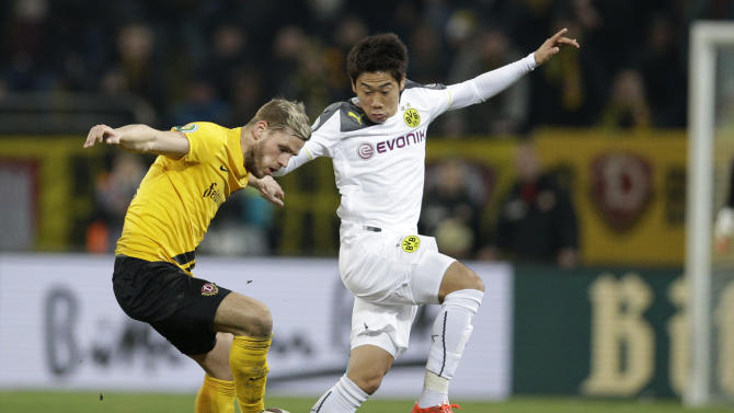 Dresden's Justin Eilers, left, and Dortmund's Shinji Kagawa from Japan challenge for the ball during the German soccer cup round of sixteen match between third division team Dynamo Dresden and first division team Borussia Dortmund in Dresden, Germany, Tuesday, March 3, 2015. (AP Photo/Michael Sohn)