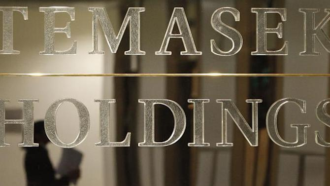 Staff member is reflected in Temasek Holdings logo before presentation of Temasek's annual review in Singapore