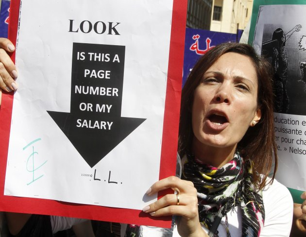 A teacher holds a placard during a protest in front of the Grand Serail in Beirut
