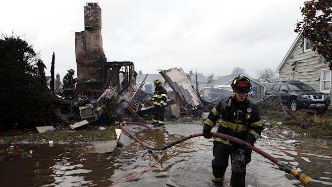 Firefighters work at the scene of a house fire in the aftermath of superstorm Sandy, Tuesday, Oct. 30, 2012, in Lindenhurst, N.Y. According to firefighters at the scene, four homes were destroyed by fire overnight in Lindenhurst, and six in Massapequa. (AP Photo/Jason DeCrow)