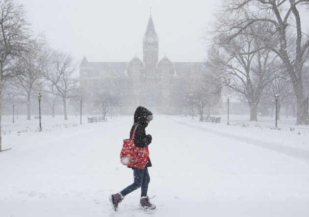 A student makes her way across the campus of Friends University in Wichita, Kan. as heavy snow falls on Wednesday morning, Feb. 20, 2013. A large winter storm moved in over the early morning hours and
