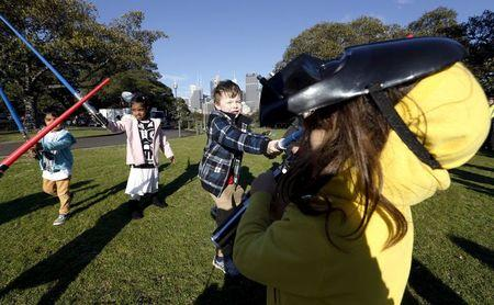 "A child wearing a Darth Vader mask participates in a light saber duel with other children after the live internet unveiling of new light saber toys from the film ""Star Wars - The Force Awakens"" in Sydney"