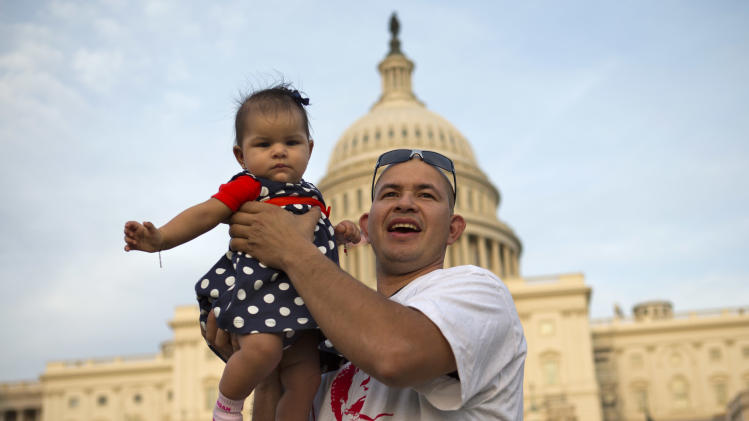 Edwin Munoz, who is originally from El Salvador, holds his daughter Jocelyn Munoz, 5 months, up for a portrait at the end of the