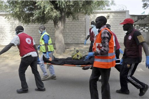 Red Cross officials carry victim of a bomb attack in Nigeria's northern city of Kano