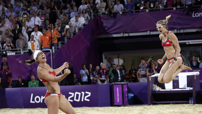 Miss May Treanor, left, and Kerri Walsh Jennings celebrate a win over April Ross and Jennifer Kessy during the women's Gold Medal beach volleyball match between two United States teams  at the 2012 Summer Olympics, Wednesday, Aug. 8, 2012, in London. (AP Photo/Dave Martin)