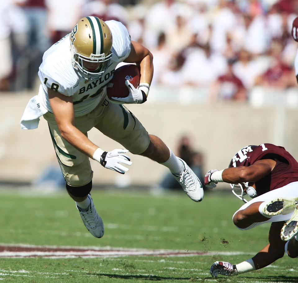Baylor's Jordan Najvir, left, dives over Texas A&M defender Trent Hunter, right, during the first half of an NCAA college football game Saturday, Oct. 15, 2011, in College Station, Texas. (AP Photo/Jon Eilts)
