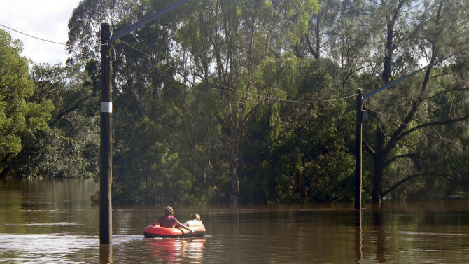 In this photo supplied by NSW State Emergency Service,  two children ride on a boat in floodwaters caused by torrential rains in Lismore, northern New South Wales, Australia Tuesday, Jan. 29, 2013. Thousands of Australians huddled in shelters Tuesday as torrential rains flooded cities and towns in the northeast. With floodwaters expected to peak in most of the worst-hit areas later Tuesday, officials were rushing to move those in the highest-risk areas to safety. (AP Photo/NSW State Emergency Service, Samantha Cantwell ) NO SALES